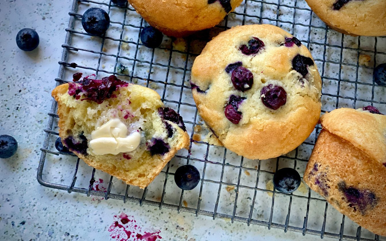 Classic blueberry muffins cooling on a wire rack.