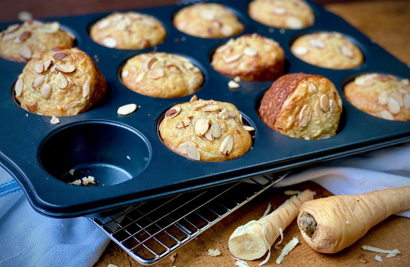 Parsnip muffins topped with sliced almonds cooling in a muffin tin.