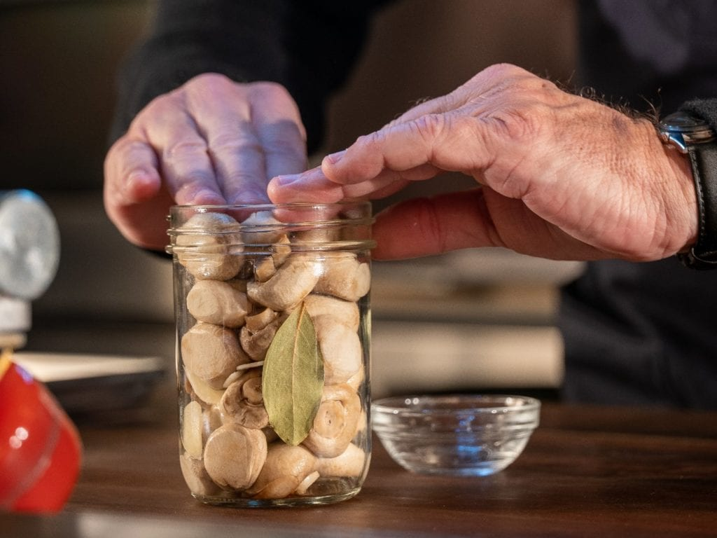 Alton Brown packing pickled mushrooms and bay leaves into a glass canning jar.