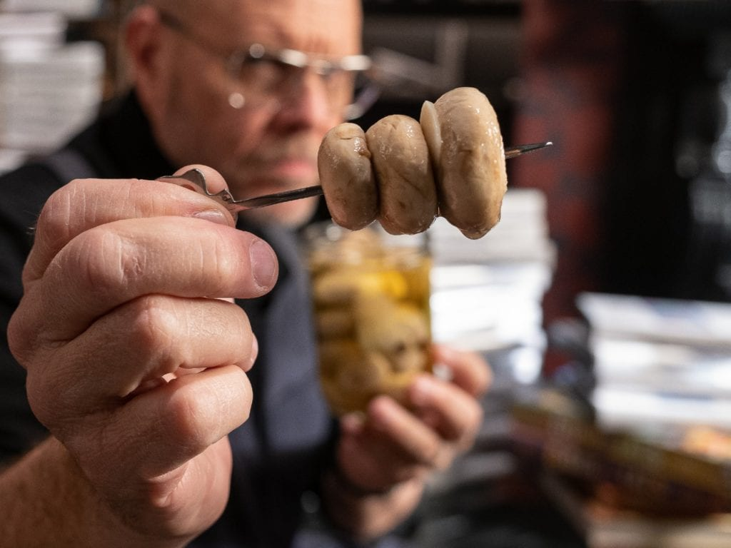Alton Brown holding three pickled mushrooms on a skewer.