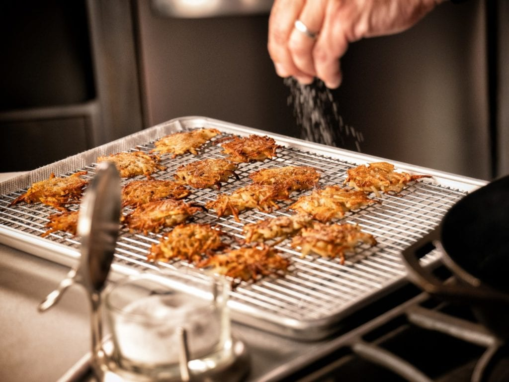 Potato Latkes being seasoned with kosher salt on wire rack