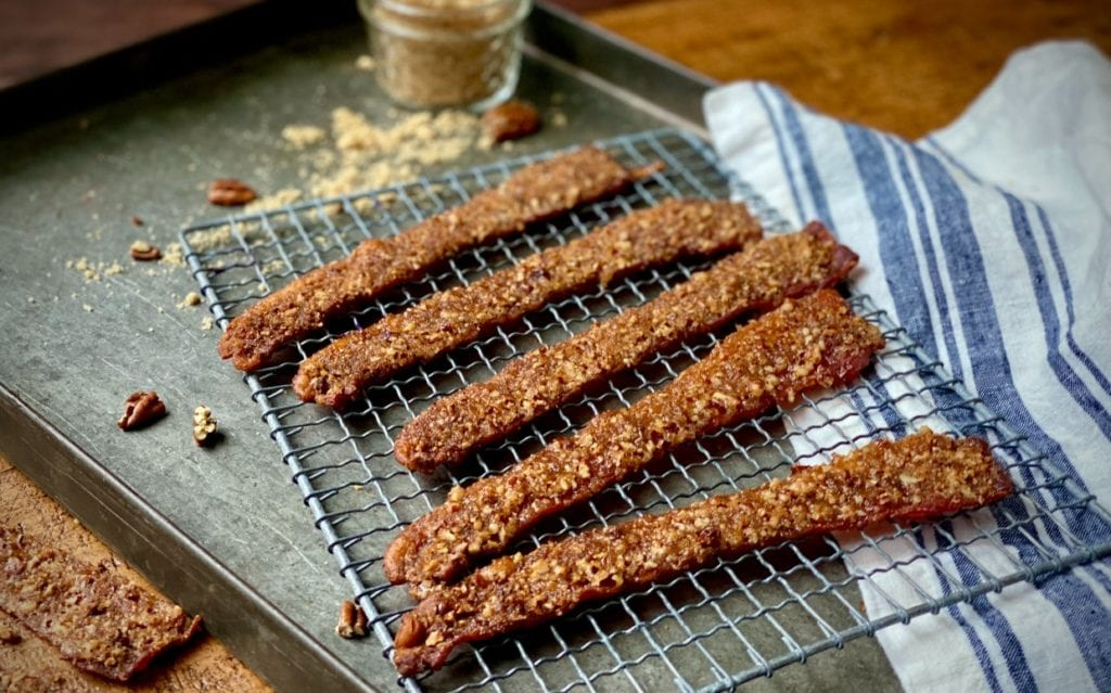 Praline bacon slices on a wire cooling rack.