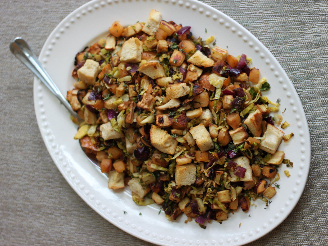 Roasted root vegetable panzanella on a large white serving plate.
