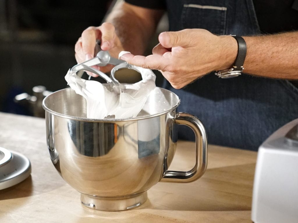 Homemade royal icing in the stainless steel bowl of a stand mixer gets a taste check from Alton Brown.