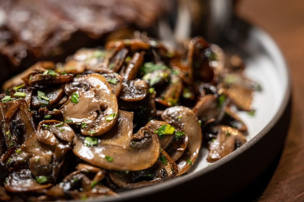 Sauteed mushrooms in a black bowl garnished with parsley.