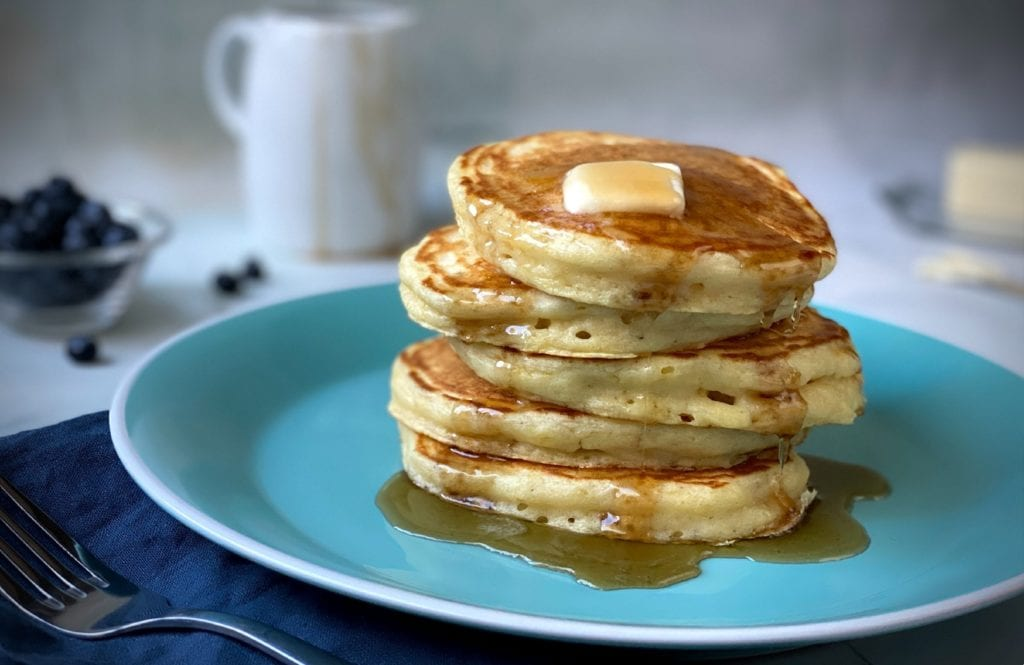 Semi-instant pancakes stacked on a plate, drizzled with maple syrup, and topped with a pat of butter.