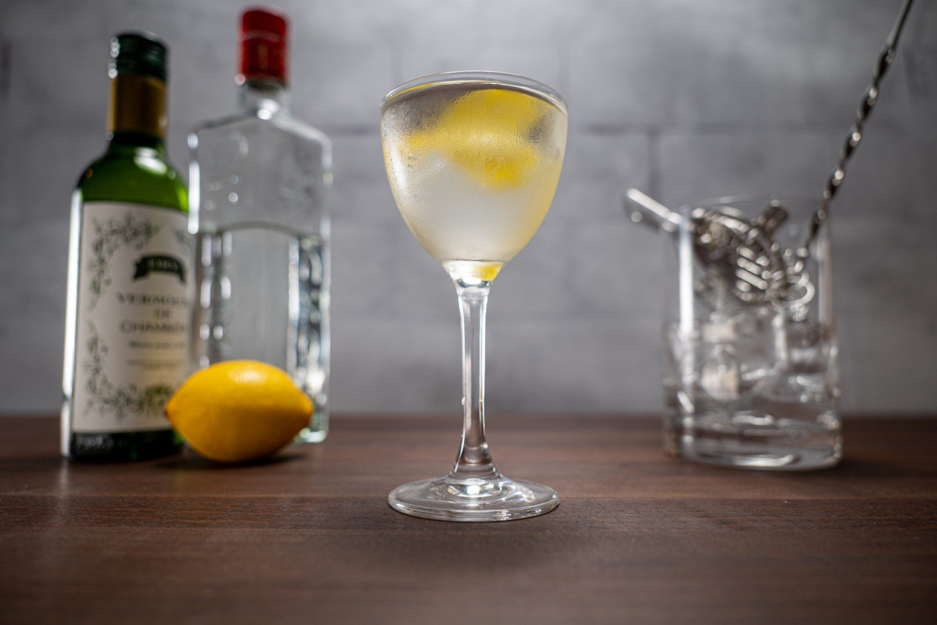 Alton Brown martini garnished with a twist of lemon and flanked by gin, vermouth, a lemon and a cocktail mixing glass.