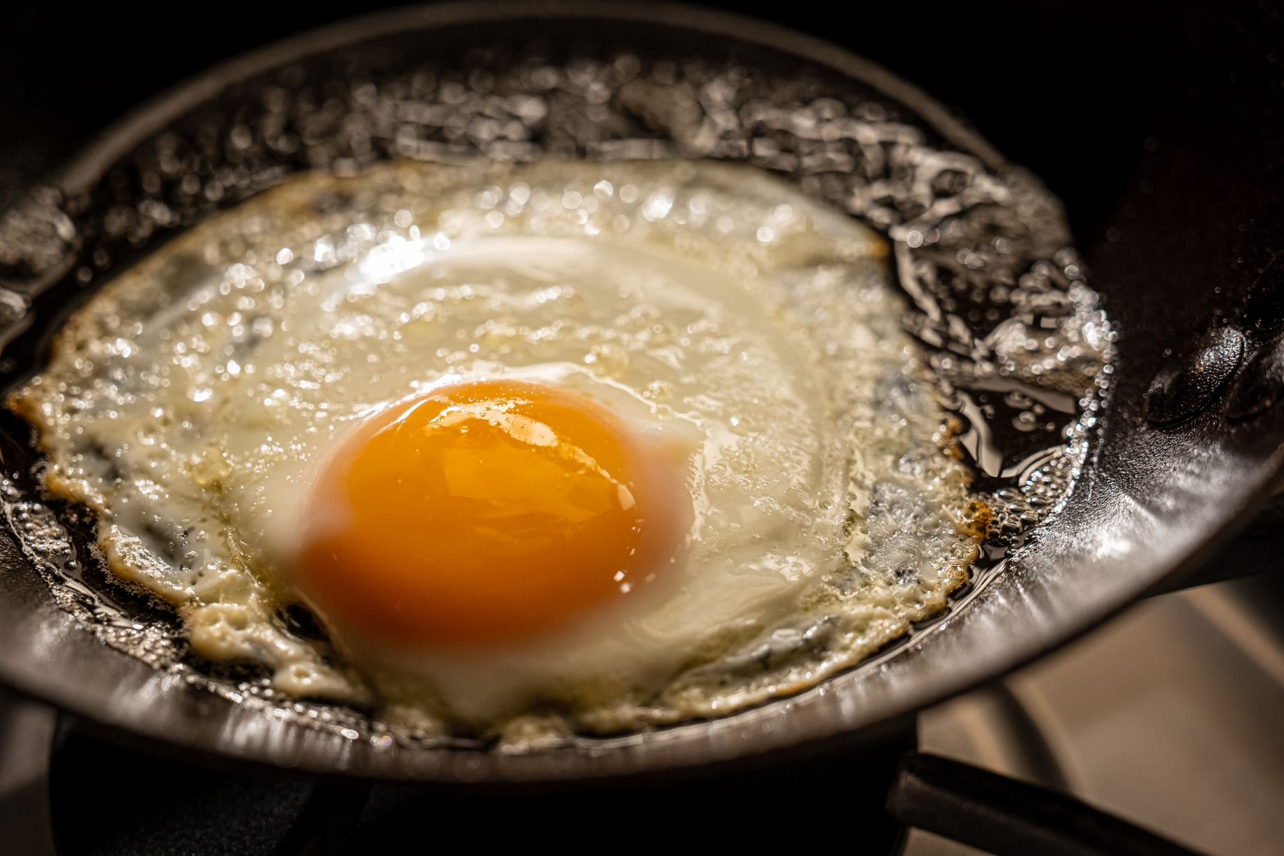 Perfect fried eggs sizzling in a cast-iron skillet on the set of Alton Brown's Good Eats Reloaded.