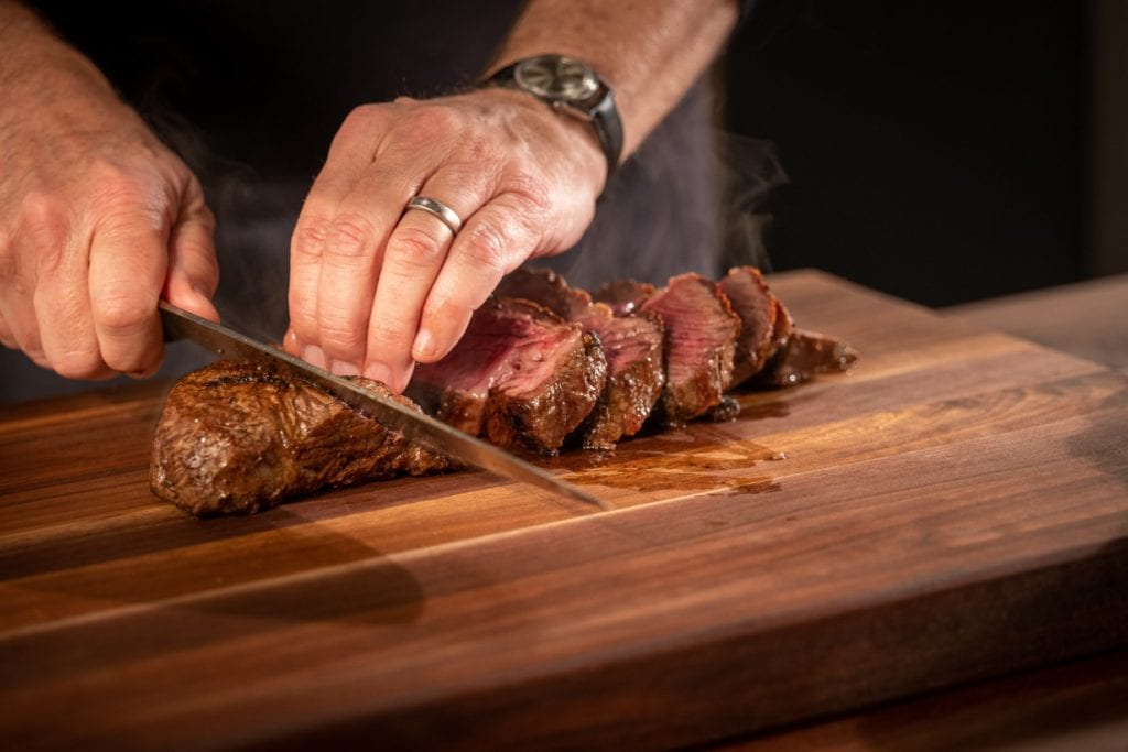 Thermal shock sirloin sliced on the bias on a butcher block cutting board.