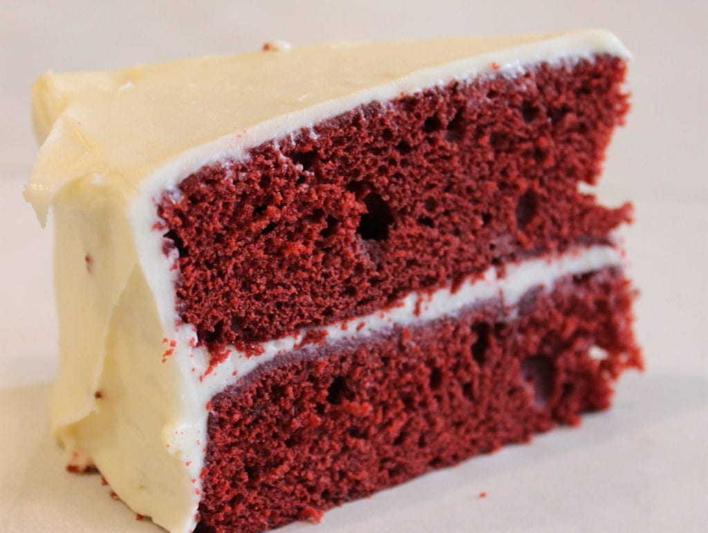 Red velvet cake slice with cream cheese frosting.