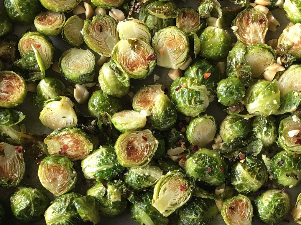 Sesame peanut brussels sprouts on a half-sheet pan.
