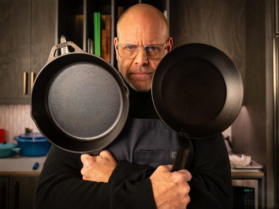 Alton Brown holds two cast iron skillets on the kitchen set of Good Eats Reloaded season 2.