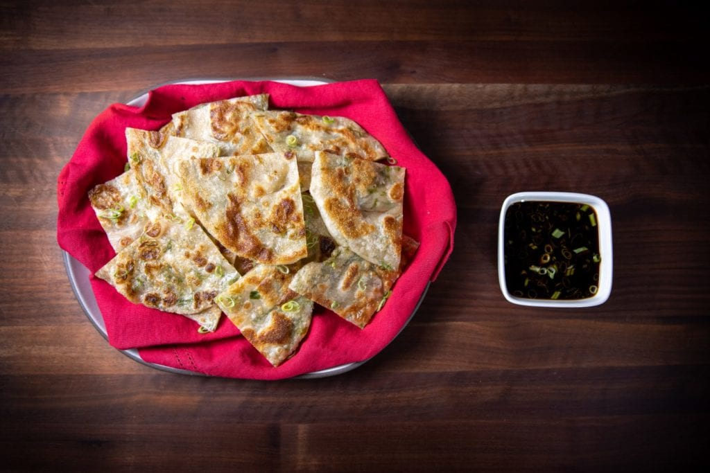 Scallion pancakes on a platter with a side of dipping sauce.