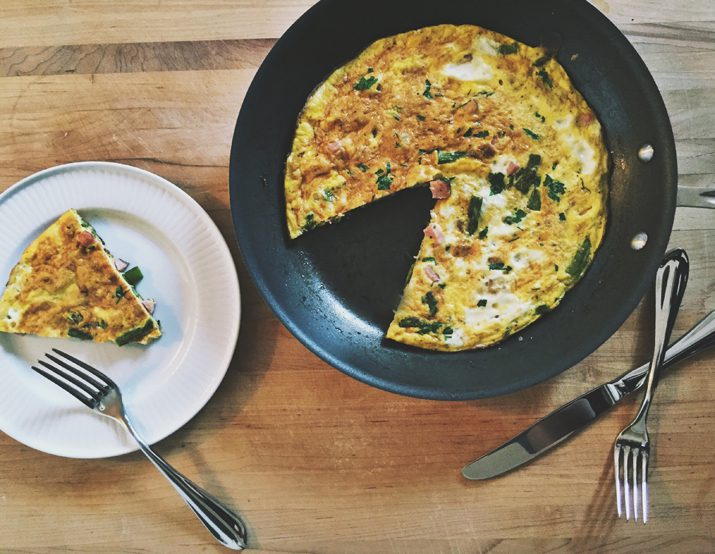 Easy ham and cheese frittata in a skillet with a wedge cut out and served on a white plate.