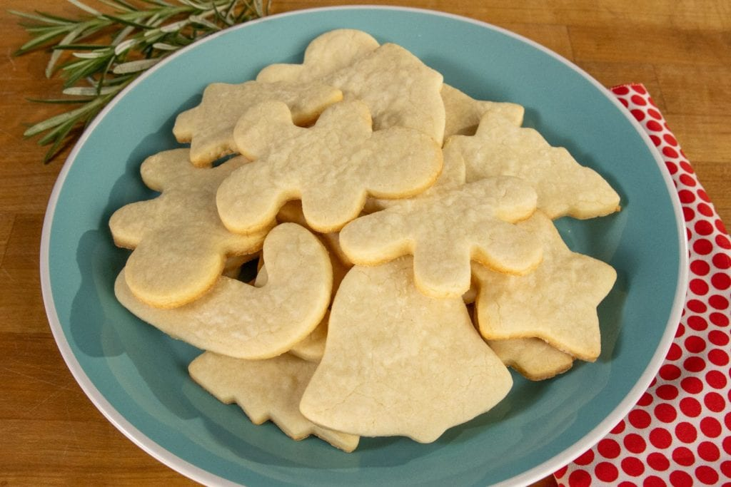 Simple sugar cookies 2.0 cut into festive shapes and stacked on a plate.