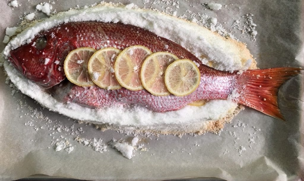 A whole red snapper resting on a bed of salt.