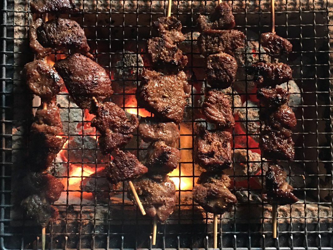 Grilled lamb skewers rest on a grill grate over a live fire.