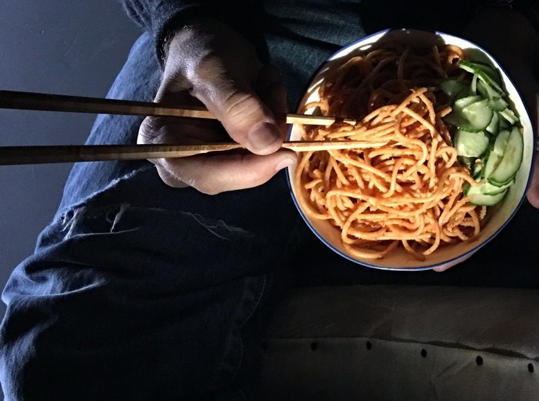 Easy sesame noodles in a bowl with a side of pickles.