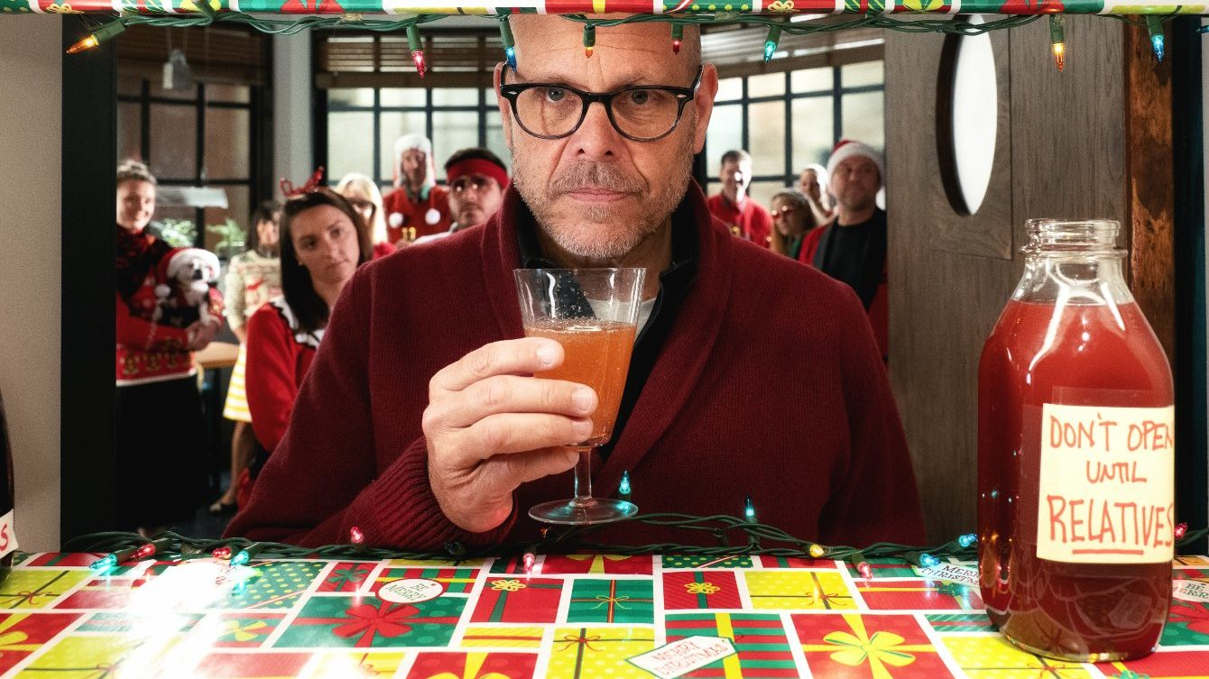 Alton Brown sips low-alcohol holiday coctail cranberry-apple shrub on the set of Good Eats: The Return.