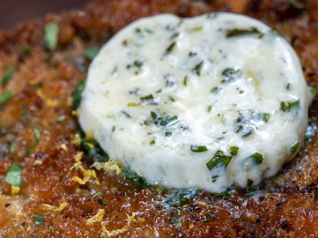 Compound herb butter melting on a piece of Alton Brown's Schnitzel Kiev.