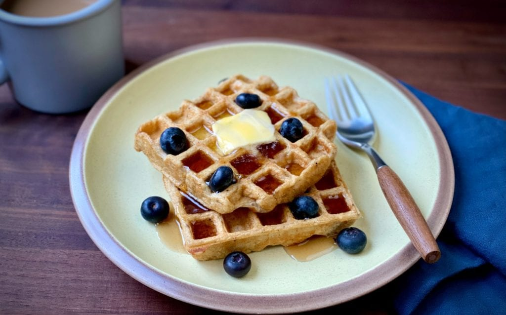 Toasted oat waffles with blueberries and butter.