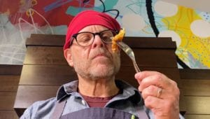 Alton Brown's holds up a piece of his French Toast on a fork.